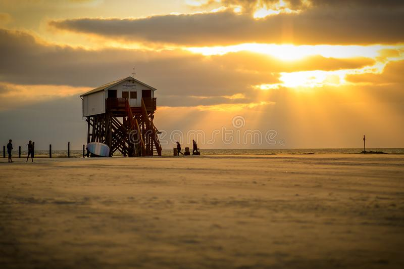 White Lifeguard House on Beach Taken Under White Clouds and Orange Sky royalty free stock image