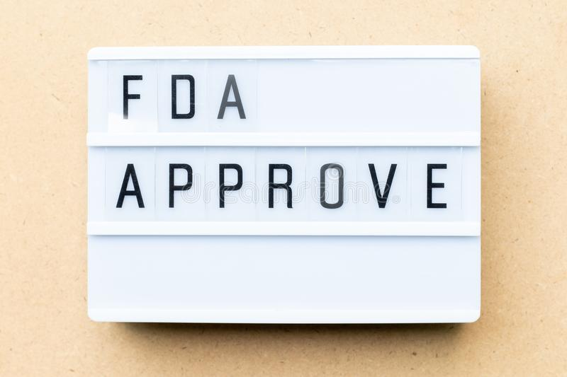 White light box with word fda approved on wood background. White lightbox with word fda approved on wood background stock image