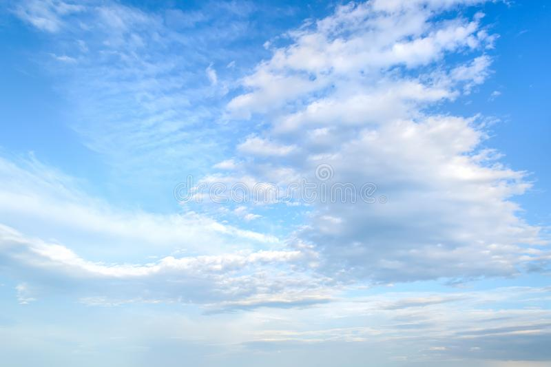 White light fluffy stratus and cirrus clouds high in the blue summer sky. Different cloud types and atmospheric phenomena.  stock photo