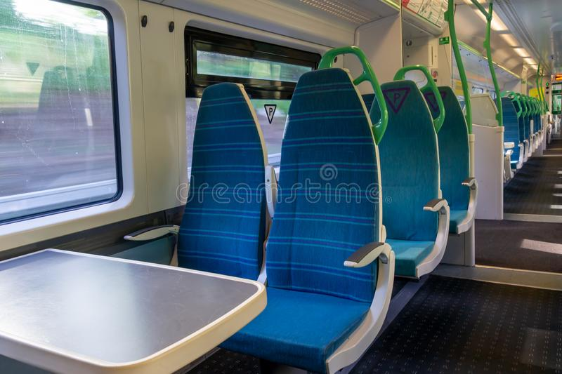 White light panoramic view interior of a high speed electric modern train with blue seats royalty free stock photos