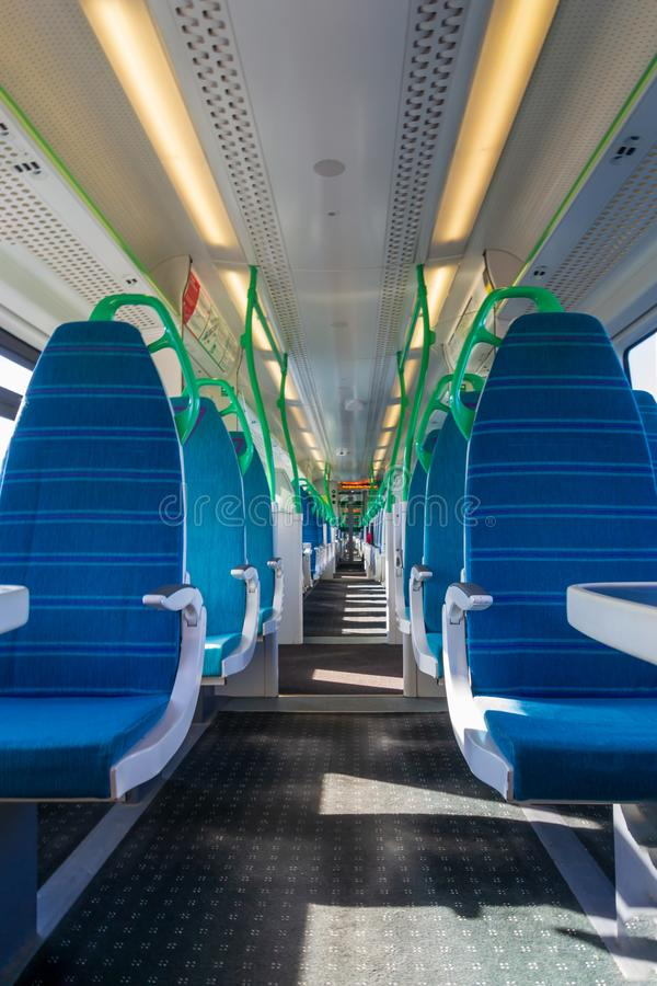White light panoramic view interior of a high speed electric modern train with blue seats royalty free stock image
