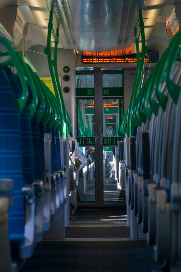 White light panoramic view interior of a high speed electric modern train with blue seats. Business, carriage, chair, city, comfort, comfortable, commute stock photography