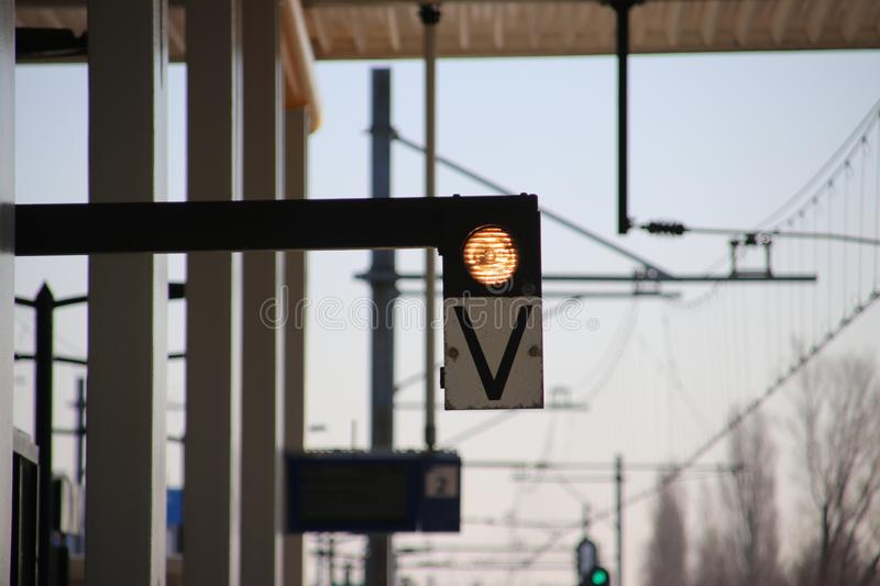 White light with sign V on a railway platform, when lit the train can depart safely. White light with sign V on a railway platform, when lit the train can royalty free stock photos