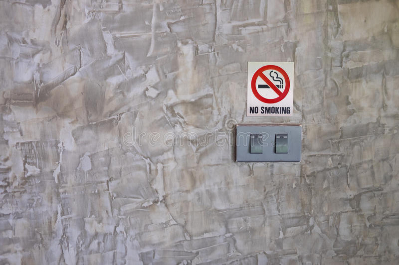 White light switch, turn on or turn off the lights. White light switch and no smoking sign on grey concrete wall loft style royalty free stock image