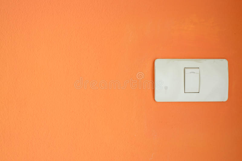 White light switch, turn on or turn off the lights on orange wall. royalty free stock photo