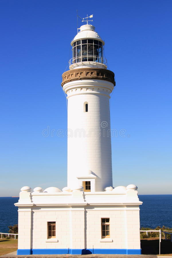 White lighthouse by blue sky and sea. White lighthouse by a blue sky and a calm sea in the background royalty free stock photography