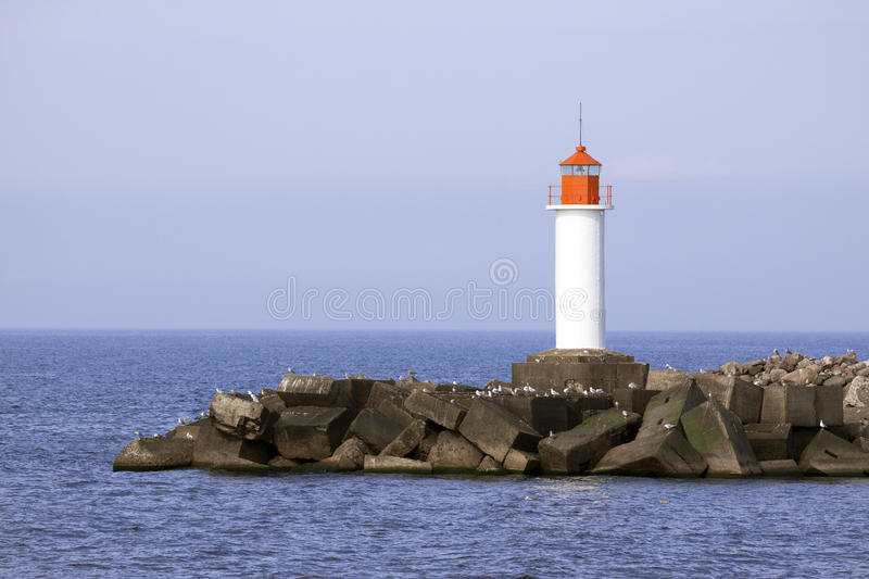 White lighthouse. And stone pier in Ventspils, Latvia royalty free stock photos