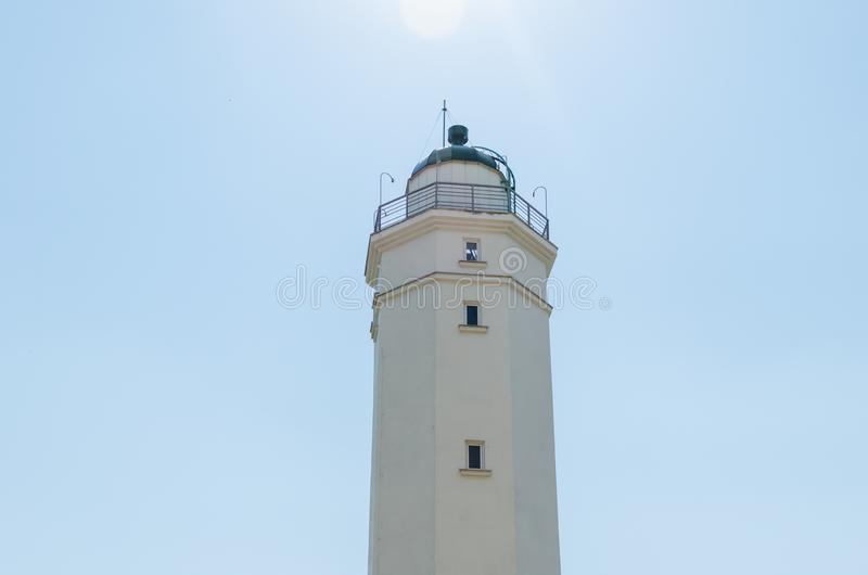 White lighthouse against the blue sky on a sunny day.  royalty free stock photography