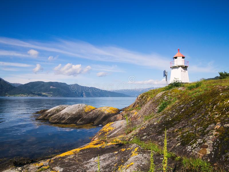 White lighthouse along rocky shore of the Sognefjord in Norway royalty free stock image