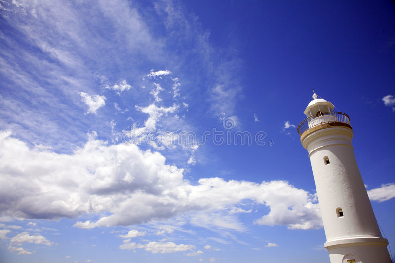 White lighthouse with blue sky. White tall lighthouse with a blue sky royalty free stock image