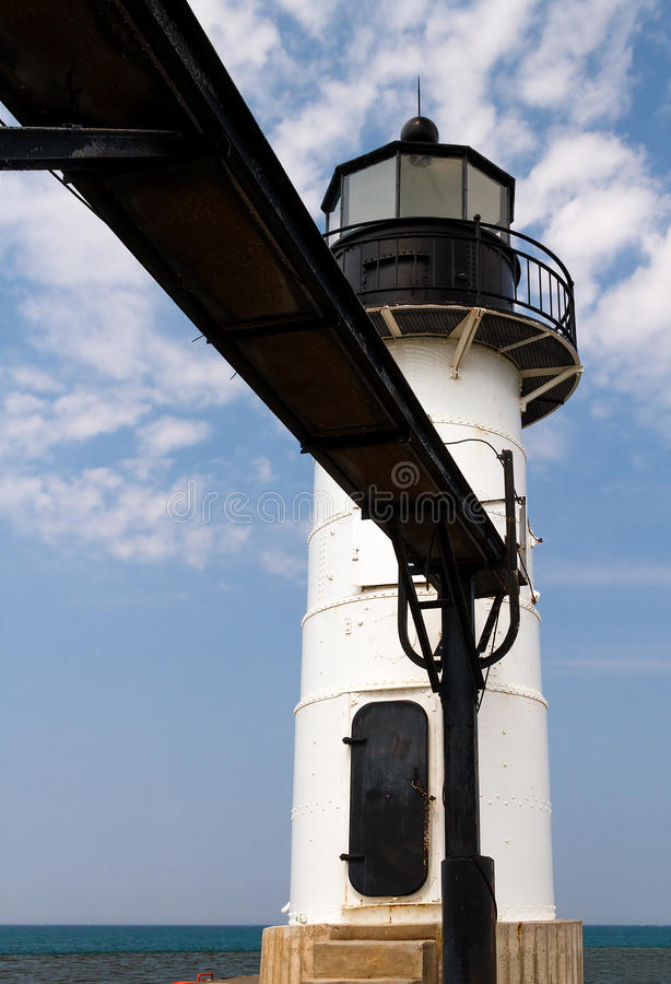 White Lighthouse and Catwalk. White lighthouse with elevated catwalk approach on the North Pier at St. Joseph, Michigan royalty free stock images