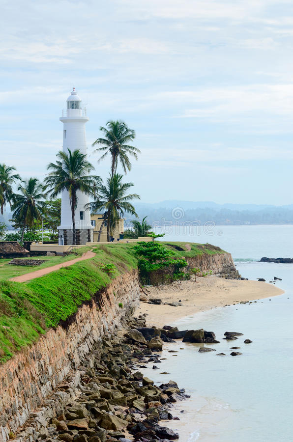 White lighthouse in Galle, Sri Lanka. White lighthouse on fortified stone wall with cloudy sky background, Galle, Sri Lanka stock images