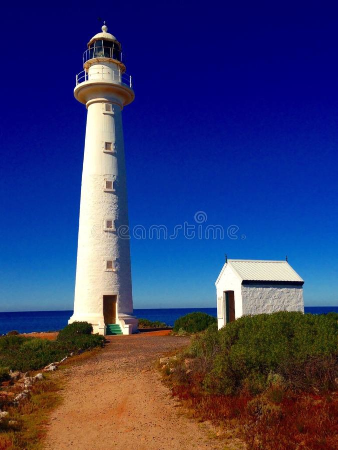 White lighthouse. And lighthouse keeper building against blue sky and path leading royalty free stock image