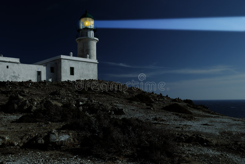 White lighthouse at the night. White lighthouse with bright ray at the night stock photos