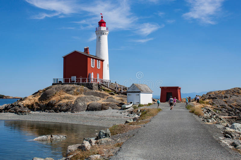 White Lighthouse on Rock Strewn Beach With Path. Path leading to bright white lighthouse and red tender building royalty free stock image