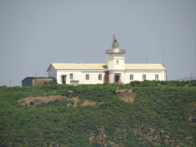 White lighthouse on the small island in the sea closeup royalty free stock photography