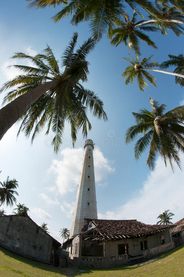 White lighthouse standing on an island surrounded by green palm trees. White lighthouse standing on an island surrounded by green palm trees in Belitung at royalty free stock photos