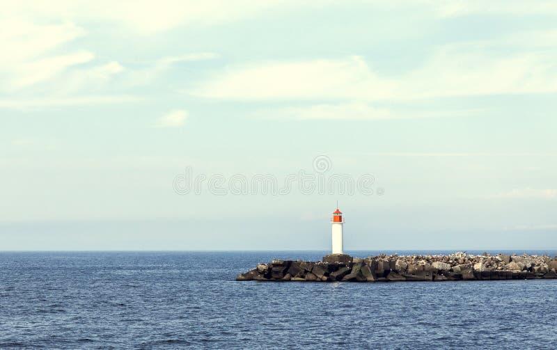 White lighthouse and stone pier. Retro looking picture of white lighthouse and stone pier in Ventspils, Latvia royalty free stock photo