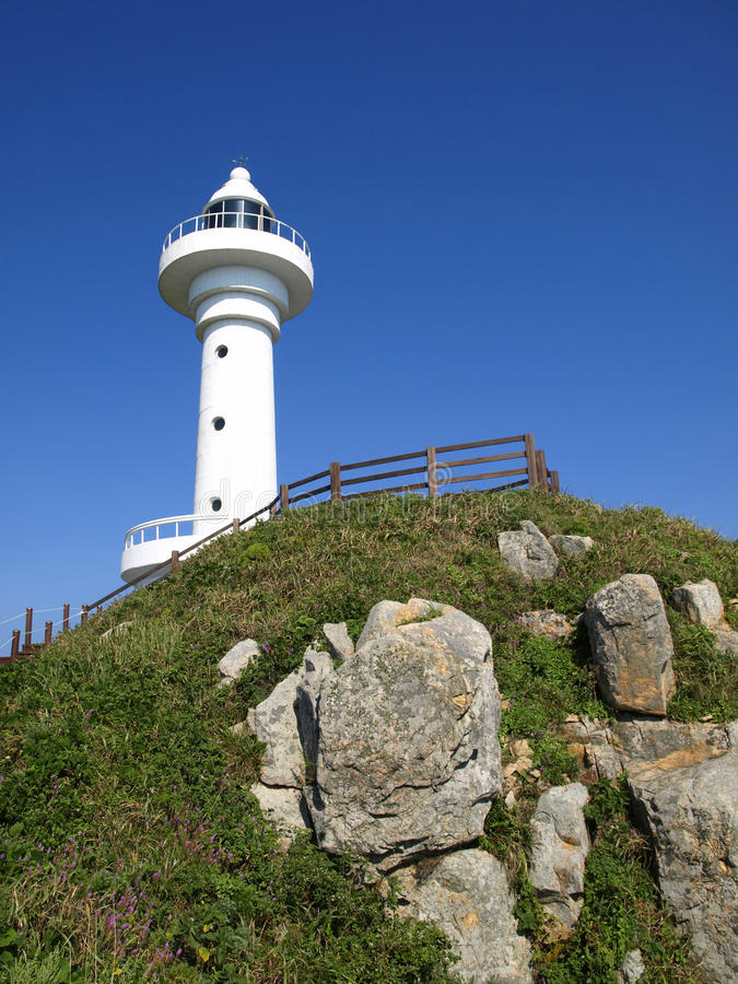 White lighthouse on top of green rocky hill royalty free stock photos