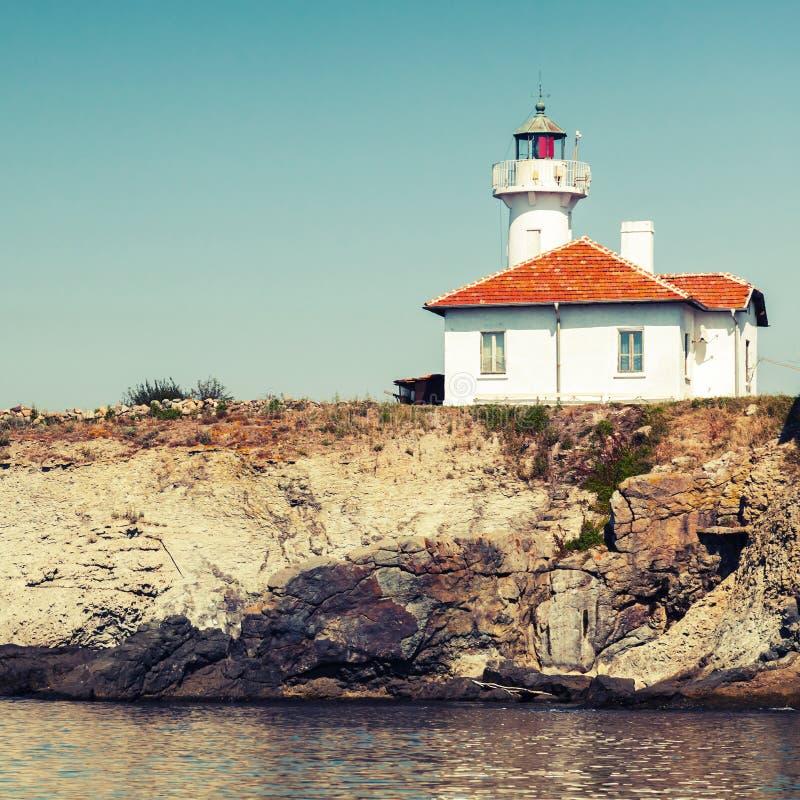 White lighthouse tower on St. Anastasia Island. White lighthouse tower with red light on St. Anastasia Island. Black Sea, Bulgaria. Vintage toned square photo stock images