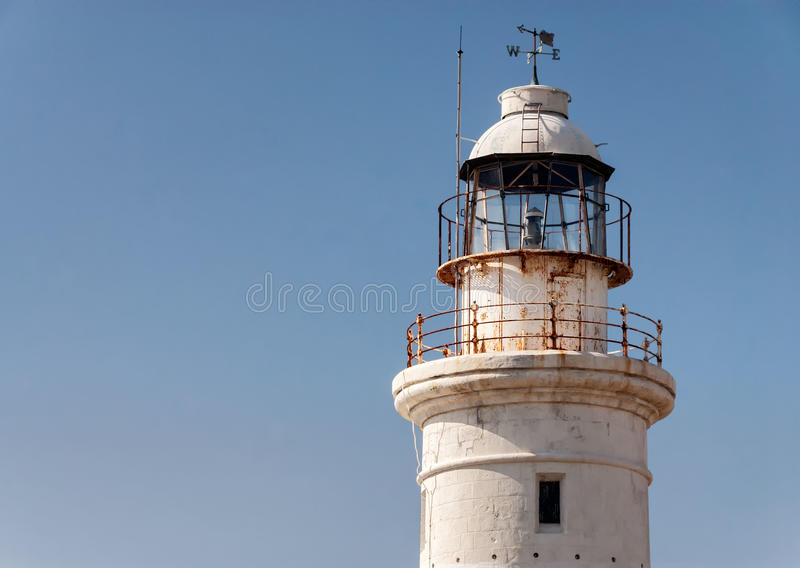 White lighthouse with weathervane royalty free stock images