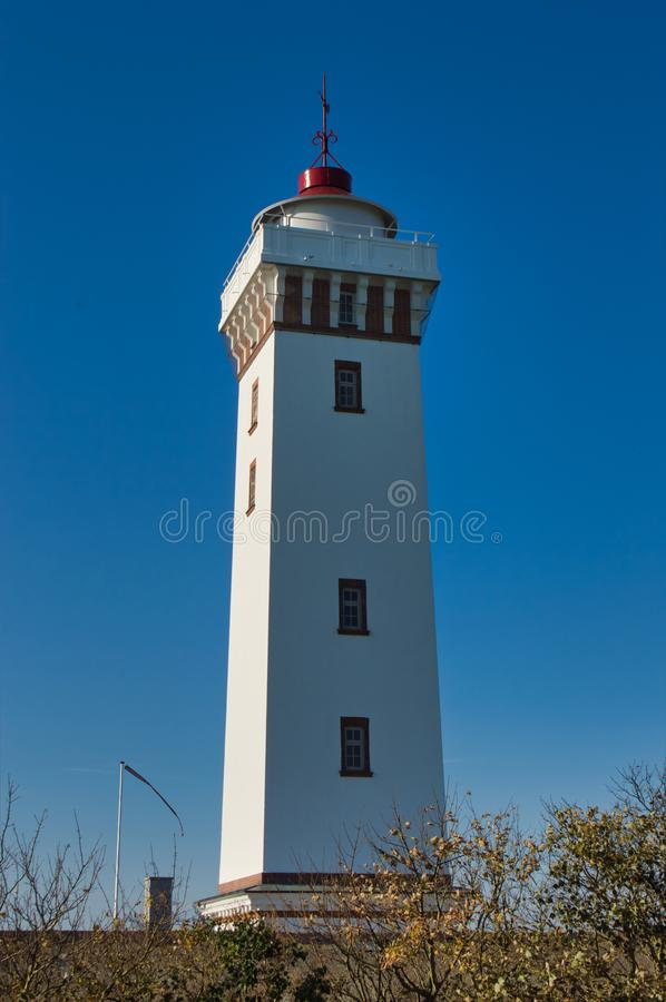 White Lighthouse. With windows and blue sky royalty free stock image