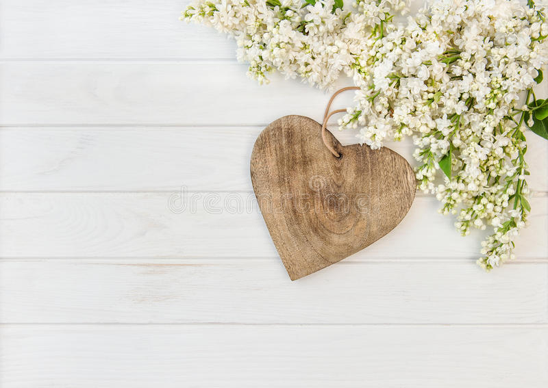White lilac flowers wooden heart royalty free stock photo