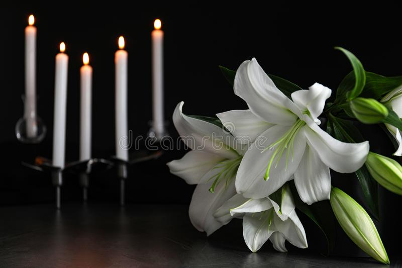 White lilies and blurred burning candles on table in darkness, closeup with space for text. Funeral symbol stock images