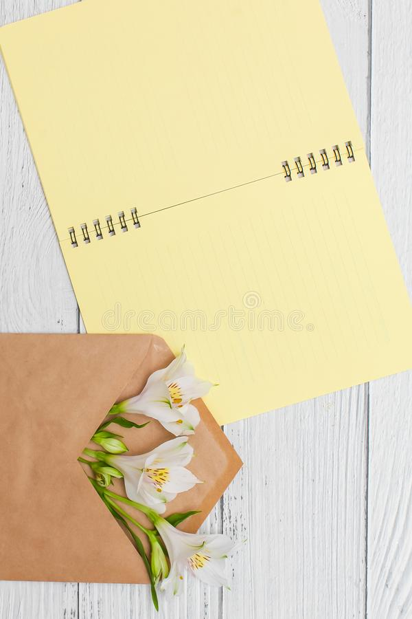 White lilies in craft envelope with yellow notebook on white wooden table, top view, flat lay stock images