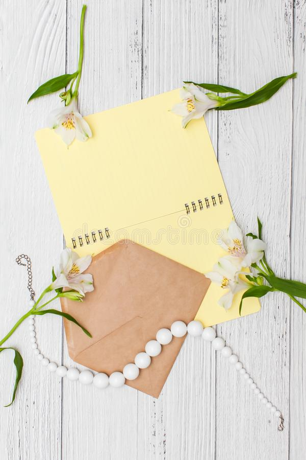 White lilies with yellow notebook and beads with craft envelope on white wooden table, top view, flat lay royalty free stock image