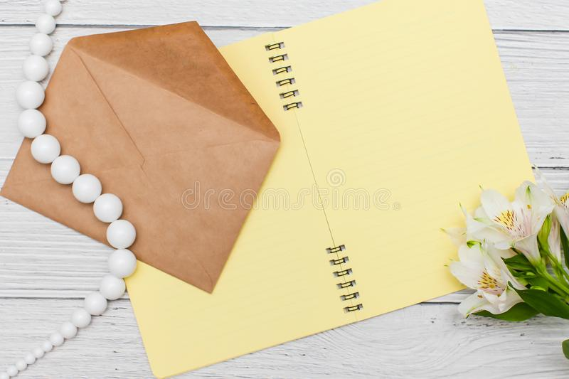 White lilies with yellow notebook and beads with craft envelope on white wooden table, top view, flat lay royalty free stock photography