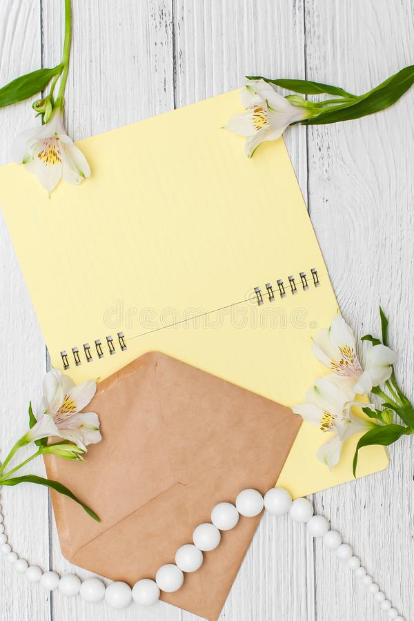 White lilies with yellow notebook and beads with craft envelope on white wooden table, top view, flat lay stock image
