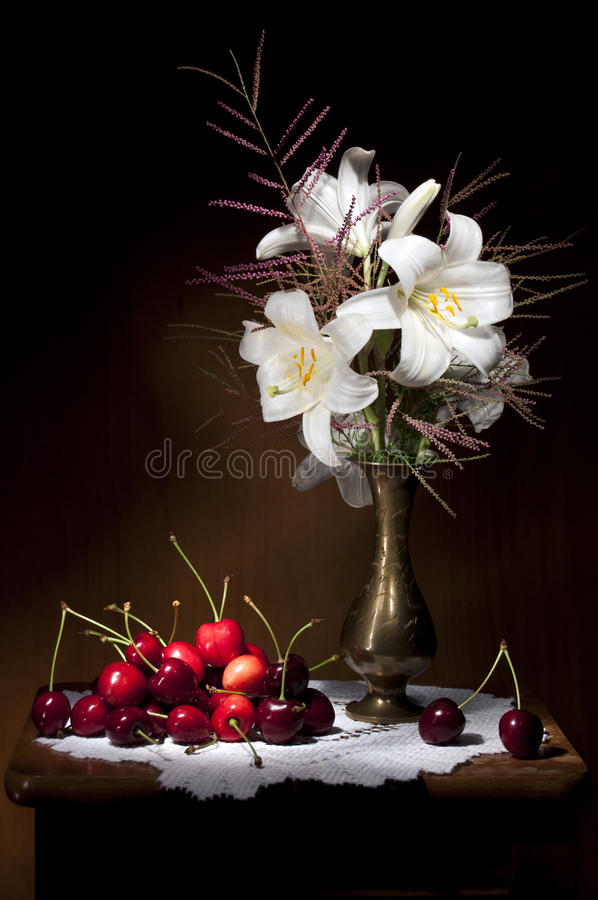 White Lily with Red Cherries Still life stock photography