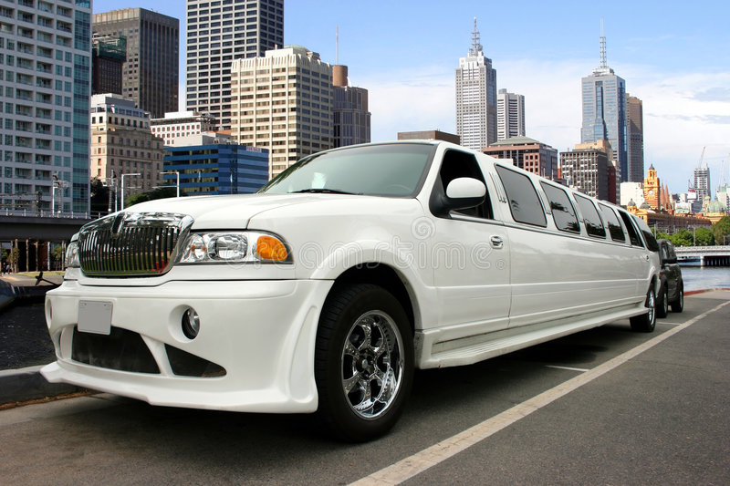 White limousine. White classy limousine waterfront and skyscrapers royalty free stock photo