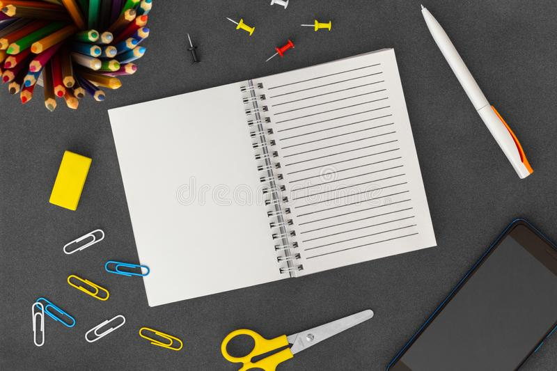 White line spiral paper notebook with mobile phone, pen, colored pencils, eraser, paper clips and scissors on dark background stock image