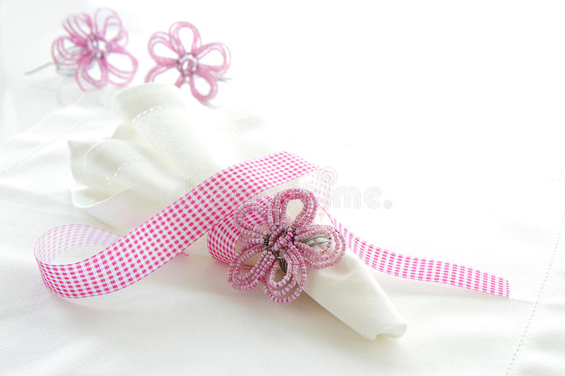 White linen serviette with pink beaded napkin ring. On a white background with space for text stock photo