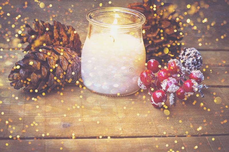 White Lit Candle in Glass Jar Pine Cones Red Holly Berries Covered with Snow on Weathered Wood Table Glittering Sparkling Lights stock image