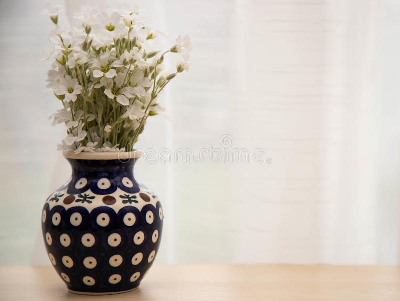 White little flowers in a vase. A bouquet of flowers yaskolki in a ceramic vase closeup. Flowers in a blue vase with a pattern on royalty free stock photos