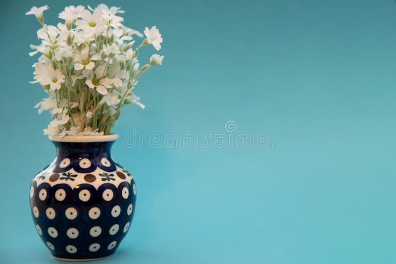 White little flowers in a vase. A bouquet of flowers yaskolki in a ceramic vase closeup. Flowers in a blue vase with a pattern on royalty free stock photography