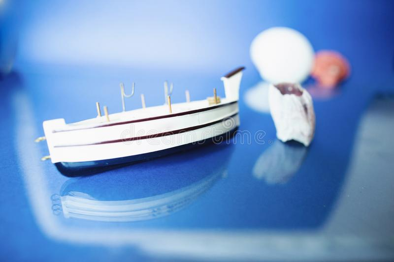 White little toy ship with shells on a blue background.  royalty free stock photo