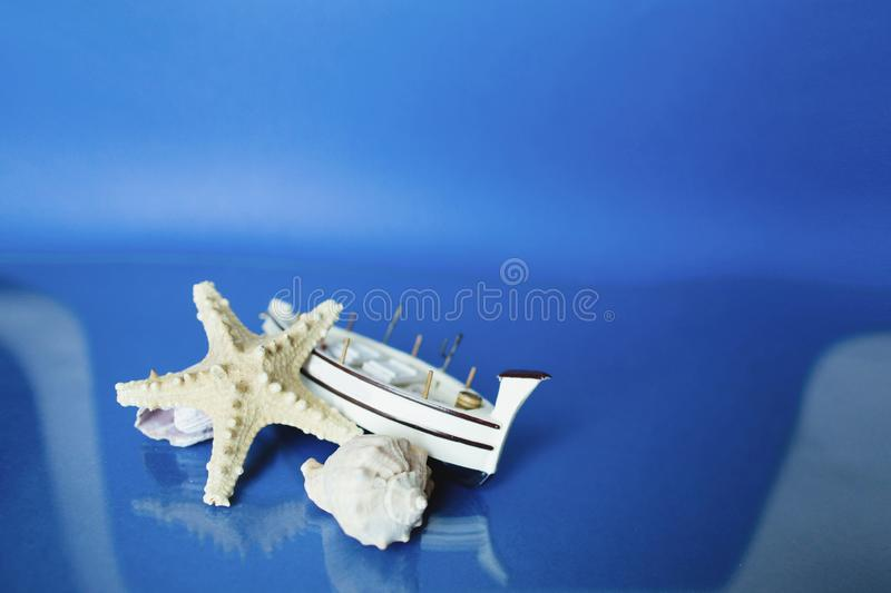 White little toy ship with shells on a blue background.  royalty free stock image