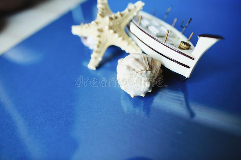 White little toy ship with shells on a blue background.  stock photo