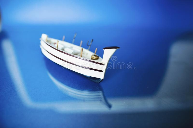 White little toy ship with shells on a blue background.  stock photography