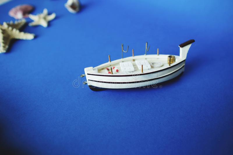 White little toy ship with shells on a blue background.  stock image