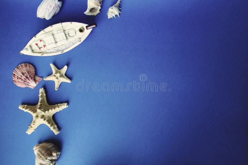 White little toy ship and shells on a blue background. Top view. Copy space.  stock photo