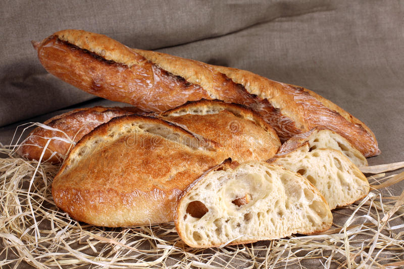 White loaves of different shapes lying in straw on grey linen ta stock photos