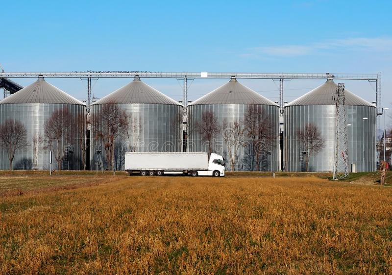 White long vehicle trailer truck in front of a grain storage bins.  stock photos