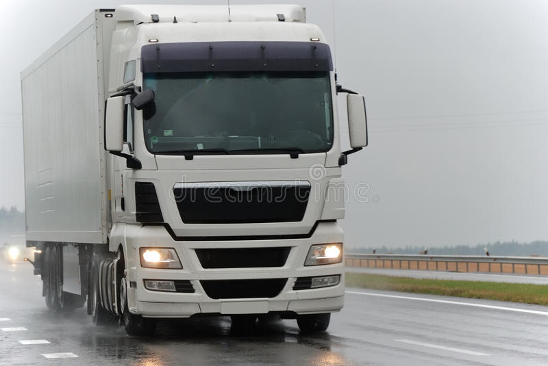 White lorry during the rain. White lorry with white trailer at wet highway during the rain. See other vans and trucks in my portfolio stock photo
