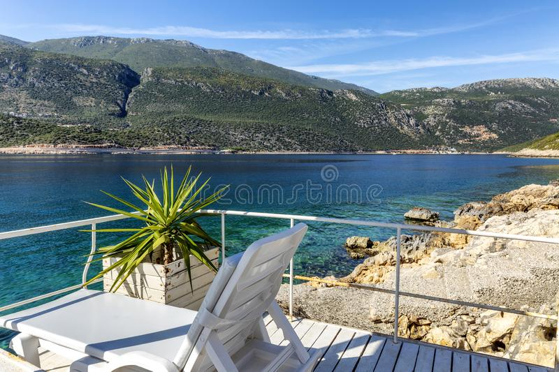 White loungers on the luxurious coast. Beautiful view of the blue sea and mountains. Gorgeous landscape. Horizontal royalty free stock image