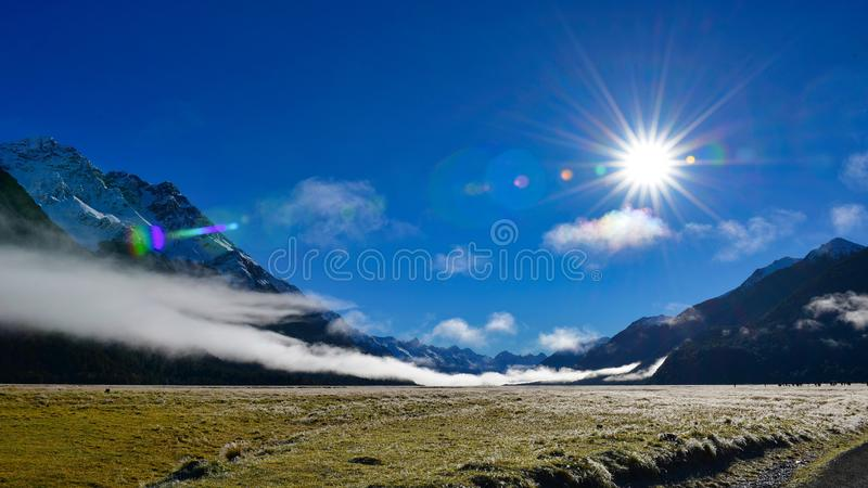 White low lying clouds and snow mountains in New Zealand royalty free stock image